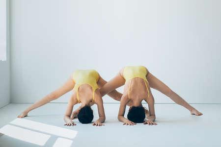 sexy girl dance: Two young beautiful women doing yoga asana wide legged forward bend. Prasarita Padottanasana I