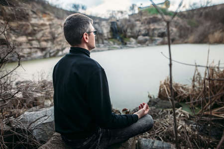 Man meditating in Lotus Pose on rocky cliff with river view. zen concept