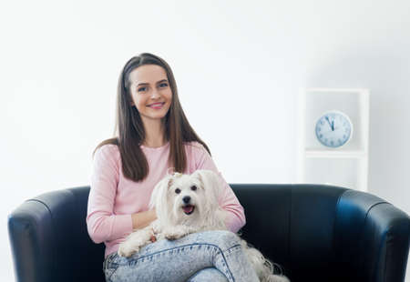 snuggle: Young beautiful woman with cute white dog sitting on sofa at home