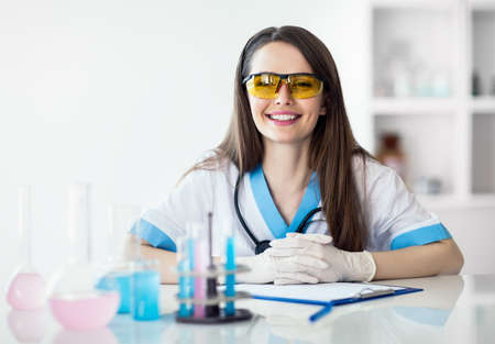 Smiling beautiful scientist in chemical laboratory