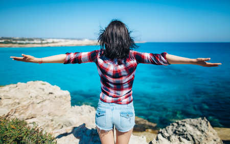 Back view of young woman with wind in her hair raising her hands on top of cliff above beautiful sea. Relax concept. Reklamní fotografie