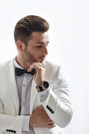 Profile portrait of thoughtful handsome man in elegant suit touching his chin