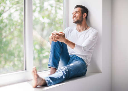 Handsome smiling man relaxing on window sill. Carefree concept