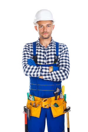 master: Young confident construction worker in uniform and tool belt with crossed arms isolated on white background