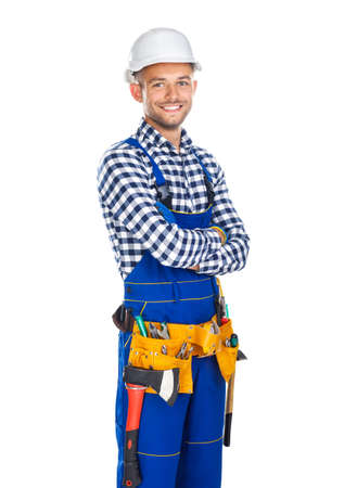 Happy smiling construction worker in uniform and tool belt with crossed arms isolated on white background Stock Photo
