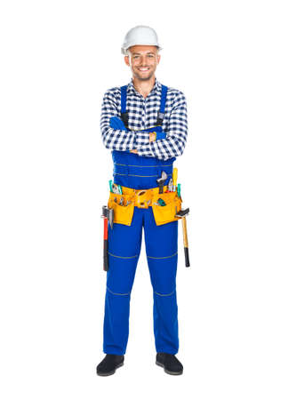 Full length portrait of happy construction worker in uniform and tool belt isolated on white background. Crossed arms