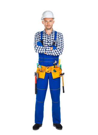 Full length portrait of confident construction worker in uniform and tool belt isolated on white background. Crossed arms Stock Photo