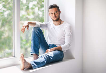 careless: Portrait of handsome thoughtful man relaxing on window sill