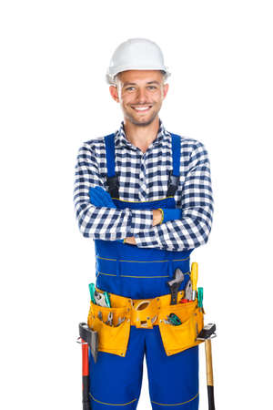 master: Happy smiling construction worker in uniform and tool belt with crossed arms isolated on white background Stock Photo