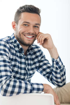 careless: Portrait of handsome smiling man sitting on chair on white background