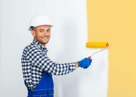 Smiling handsome painter painting the wall in beige with copy space Stock Photo