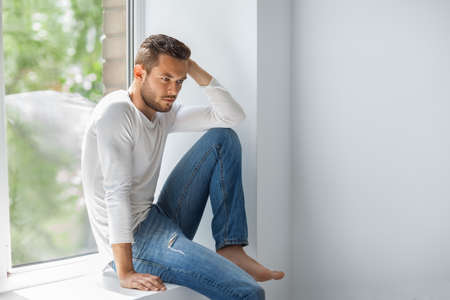 Portrait of handsome thoughtful man relaxing on window sill