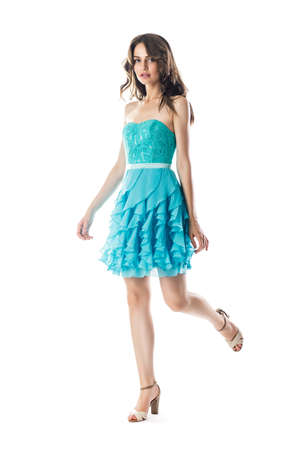 Fashion portrait of young beautiful woman in turquoise cocktail dress in motion isolated on white background