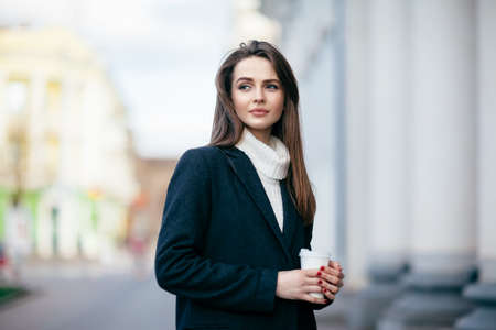 Young beautiful woman with cup of coffee in city street. Urban life Stock Photo