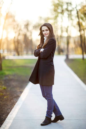 Full length portrait of young beautiful woman in park on sunset Stock Photo