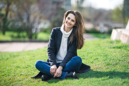 Beautiful smiling woman sitting on a grass outdoor. relax concept