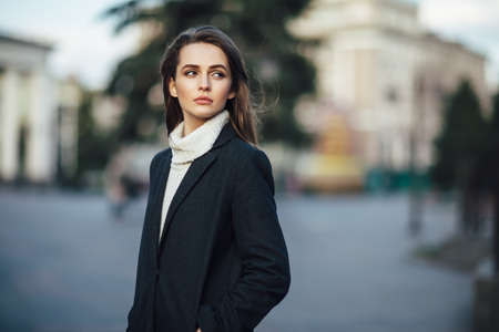 Close up pretty woman portrait posing in the city street at sunset time Stock Photo