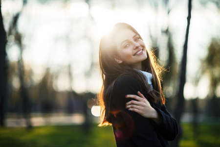 careless: Smiling beautiful woman portrait in sun light on sunset time in city park