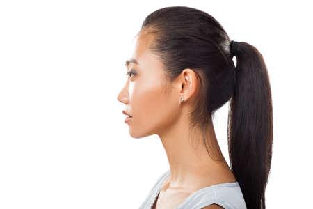 Close-up portret van Aziatische jonge vrouw in profiel met paardenstaart. Studofoto van mooi meisje met gelooide verse huid en donker haar voor diverse schoonheid en medische die projecten op witte achtergrond worden geïsoleerd