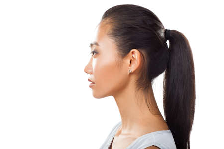 Closeup portrait of Asian young woman in profile with ponytail. Studo photo of pretty girl with tanned fresh skin and dark hair for various beauty and medical projects isolated on white background