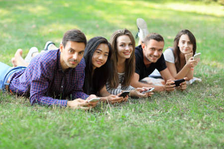 Five young friends lying on grass and using mobile phones. Two men and three women resting outdoors and browsing in smartphones, exchanging photos, chatting. Modern mobile technology, recreation, fun