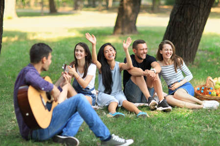 Friends or students spending weekend in park. Happy women and men singing to the guitar on picnic. Young guy playing and friends applaud. Photo on sunny warm day