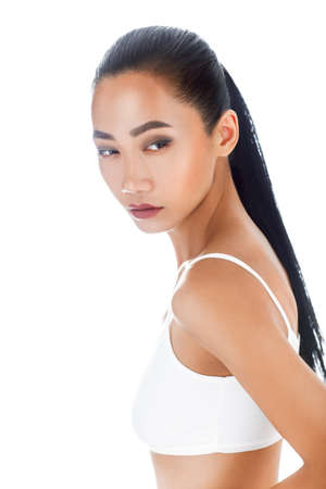 Half-body isolated portrait of Asian woman in white top. Attractive female look with clean smooth skin and makeup face