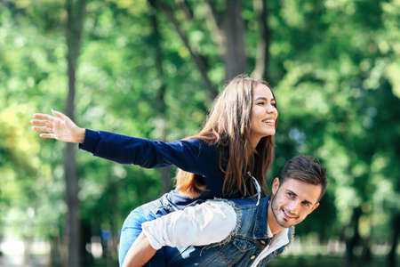 Happy young girl on back of guy portraying bird. Young couple in jeans clothes playing in nature. Girl imitate bird on back of loved one with arms outstretched