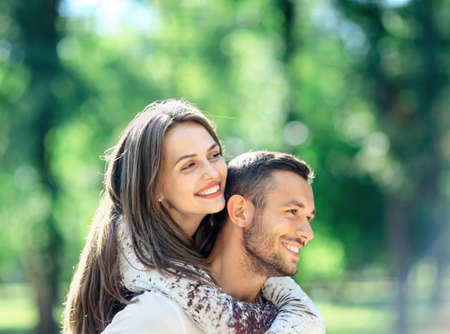 Loving couple man and woman having fun piggybacking in park. Happy smiling boyfriend and girlfriend enjoying each others company and nice summer weather. Romantic closeup portrait