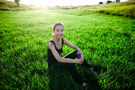 Oriental sports girl on grass with bottle looking into camera and smiling. Woman after run sitting. Concept of outdoor sports, healthy