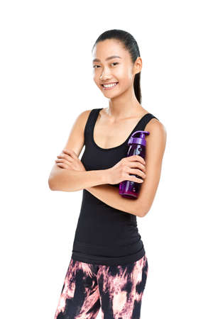 Asian woman in sportswear with bottle of water. Fitness girl resting and standing with arms crossed and sporting plastic bottle. Isolated portrait of female model bright smiling and looking at camera