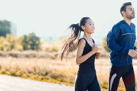 Two friends man and woman jogging on sunny day. Girl of oriental appearance and european guy dressed in sportswear. Sport and healthy lifestyle concept. Photo with copy space Stock Photo