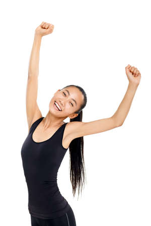 Young athletic Asian woman celebrating victory. Isolated vertical portrait of sporty girl with her hands raised upwards, model happy smiling and looking at camera