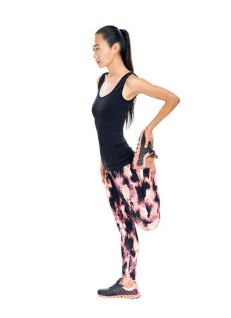 Sporty young Asian woman doing stretching legs. Full-length isolated portrait of fitness girl warming up before workout. Photo in profile of slender model in tracksuit Stock Photo