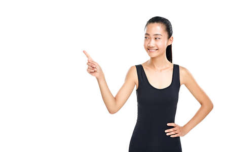 Asian woman foxy smiling and pointing finger at something. Slender girl in sporty black tanktop. Presentation, explanation, instruction concept. Half body portrait isolated on white background Stock Photo