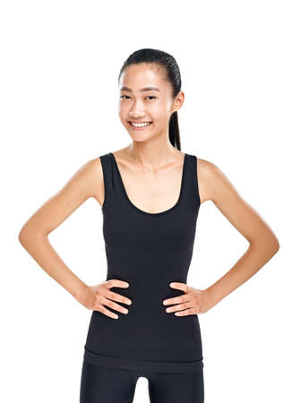 Young slender Asian woman in sporty style standing putting hands in hips. Isolated half body portrait of female athlete in black training clothes. Model happy smiling at looking at camera