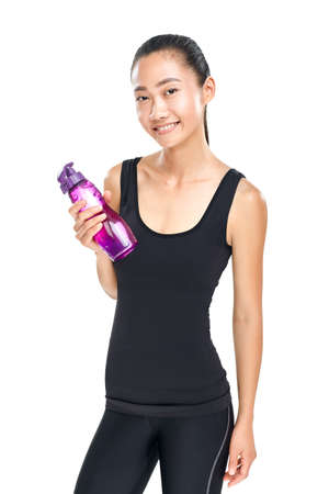 Smiling asian woman holding bottle of water. Fitness girl in black sportswear standing with sipper plastic bottle. Isolated photo of female young sporty model Stock Photo