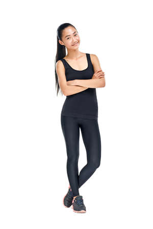 Young fit Asian woman in sporty style standing with arms crossed. Isolated portrait in full length of female athlete in black sportswear. Model happy smiling at looking at camera Stock Photo