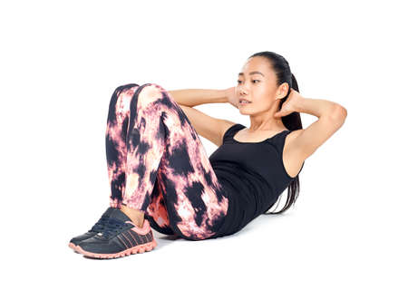 Isolated portrait of athletic slim Asian woman doing sit-ups. Fit girl doing exercises abs - workout training for abdominal muscles. Young sportswoman in sportswear. Healthy lifestyle, sport concept