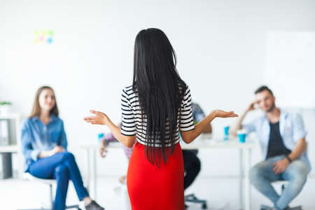 Rear view of woman business coach gesturing with hand while standing against defocused group of people sitting at the chairs in front of her Archivio Fotografico