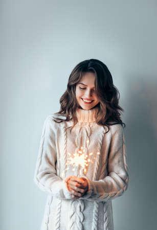 お祝いの燃えるスパークラーを保持し、楽しみを持っている幸せな美しい女性。新年、誕生日、ホリデーイベントのコンセプト