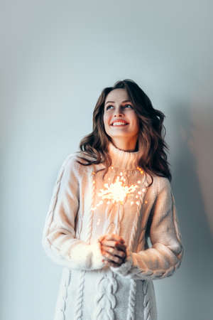 Happy beautiful woman holding festive burning sparkler and having fun. New year, Birthday, Holiday Event concept