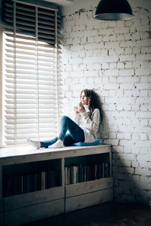 Woman drinking hot coffee sitting on window sill at home. Relax concept Foto de archivo