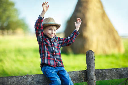 Kid boy in straw hat balances on wooden hedge, close-up. Child kept without hands on wooden fence against background of farm field with haystack. Young cowboy waves his arms