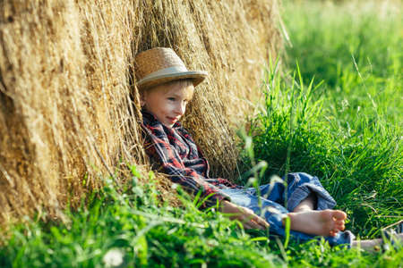 Barefooted boy in straw hat resting in haystack, outdoors, side view.