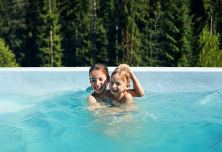 Portrait of brother and sister fooling around in outdoor pool. Children frolic in pool against backdrop of wildlife. Boy and girl having fun, laughing and cuddling  Stock Photo