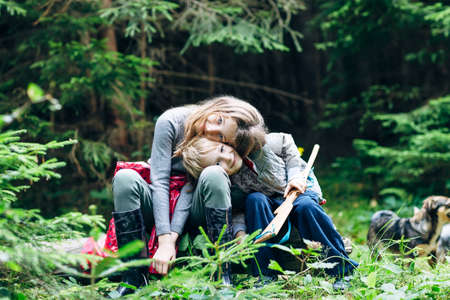 Hugging children are sitting in forest glade, their heads inclined. Brother and sister are playing in clearing surrounded by trees and with dog. Family bonds