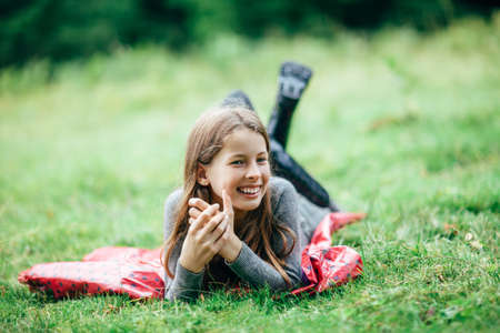 Young girl lying on pink jacket on green meadow and smiling. Cute child relax on grass with cross legged in rubber boots and laughing. Carefree, happy childhood Standard-Bild