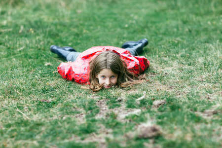 Girl in pink jacket lying on grass, head to camera. Child lying on belly on lawn, looking straight and smiling. Caucasian girlie in rain coat and rubber boots relaxing in open air