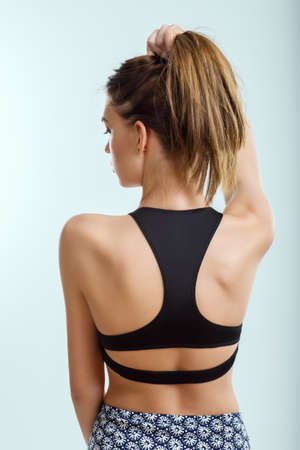 Back view of young attractive woman in swimsuit posing in studio. Beach, rest, sport, relax concept Banco de Imagens